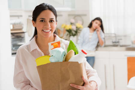 bestowing: Hispanic woman holding grocery bag