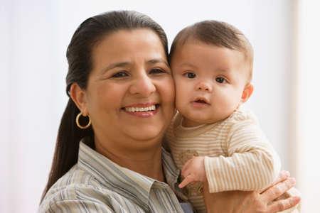 kinderen: Spaanse moeder knuffelen baby- LANG_EVOIMAGES