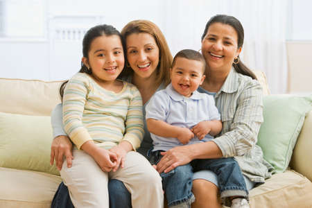 middle eastern families: Hispanic family on sofa LANG_EVOIMAGES
