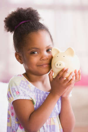 piggybank: African American girl holding piggybank LANG_EVOIMAGES