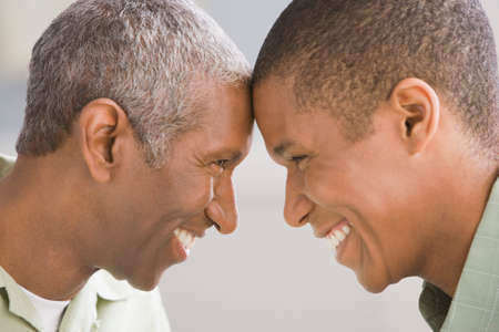 African American father and adult son touching foreheads