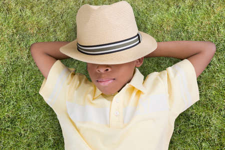 wearying: African American boy laying in grass