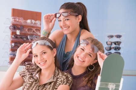 teenaged girls: Multi-ethnic teenaged girls trying on sunglasses LANG_EVOIMAGES