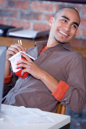 handsfree: African American man eating take out food