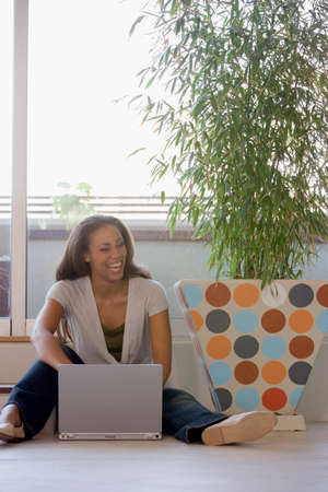 casualness: African American woman using laptop on floor