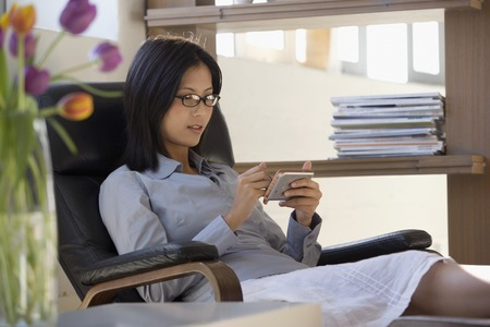 telecommuter: Asian businesswoman looking at electronic organizer