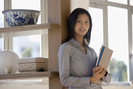 teleworking: Asian businesswoman looking holding folders LANG_EVOIMAGES