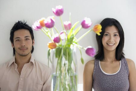 relishing: Asian couple next to flowers in vase