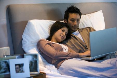 laptop: Asian couple looking at laptop