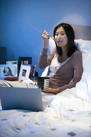 nite: Asian woman eating ice cream in bed