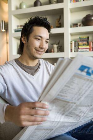 relishing: Asian man reading newspaper
