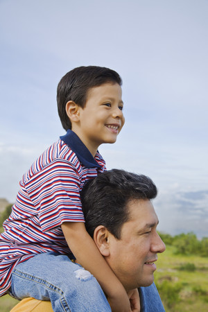 finding a mate: Hispanic father holding son on shoulders