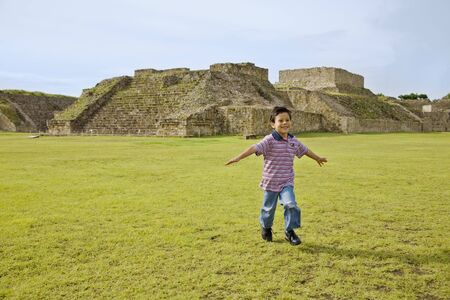 fathering: Hispanic boy running in front of ruins, Oaxaca, Mexico LANG_EVOIMAGES