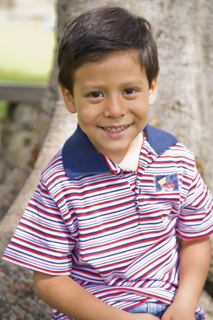 age 40 45 years: Hispanic boy in front of tree LANG_EVOIMAGES