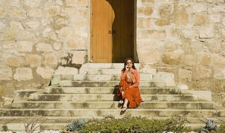 sidewalk talk: Hispanic woman sitting on stone steps