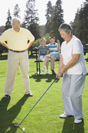 Senior Asian woman playing golf Imagens