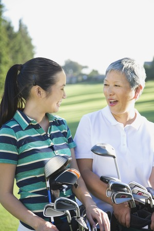 jeopardizing: Asian mother and adult daughter holding golf bags LANG_EVOIMAGES