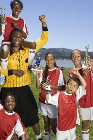 prevailing: Multi-ethnic children holding soccer trophies