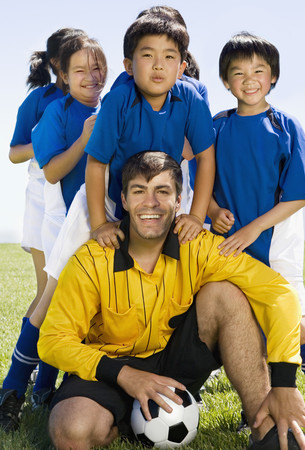 front raise: Multi-ethnic children with soccer coach