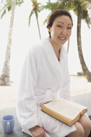 turn away: Asian woman in bathrobe with book LANG_EVOIMAGES