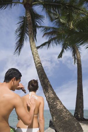 lust: Asian man applying sunscreen to girlfriend LANG_EVOIMAGES