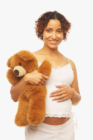 milepost: Pregnant Mixed Race woman holding teddy bear