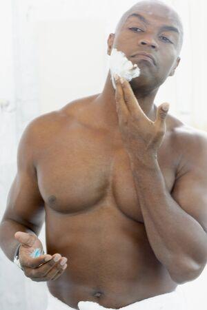 pakistani ethnicity: African American man applying shaving cream LANG_EVOIMAGES