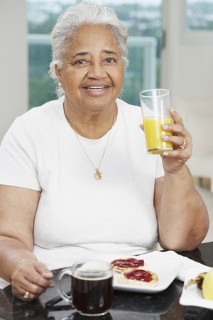 hindering: Senior African American woman eating breakfast