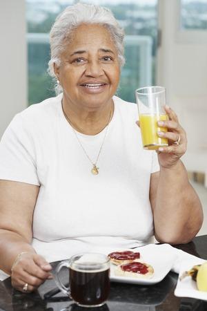 hindering: Senior African American woman eating breakfast