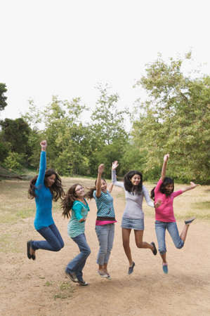 teenaged girls: Hispanic teenaged girls cheering and jumping LANG_EVOIMAGES