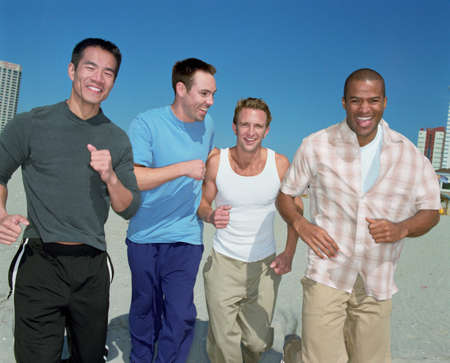 acknowledging: Multi-ethnic men running on beach