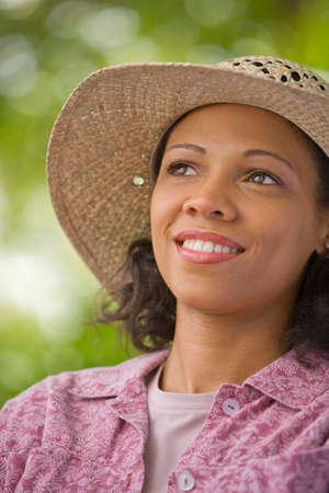 telecommuter: African American woman wearing straw hat