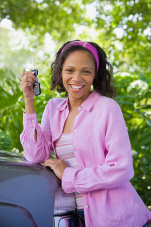 African American woman leaning on car