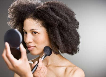 mujer maquillandose: Mujer afro-americana de aplicar el maquillaje