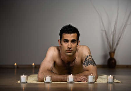 Indian man laying on yoga mat LANG_EVOIMAGES