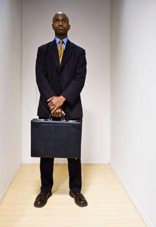hombre sentado: Hombre de negocios africano sosteniendo el maletín