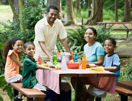 Multi-ethnic family eating at picnic table LANG_EVOIMAGES