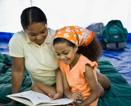 Mixed Race mother and daughter reading in tent