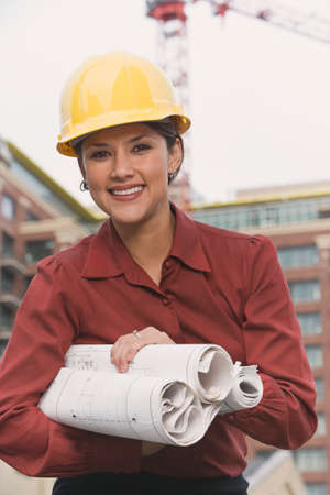 finding a mate: Hispanic businesswoman in hard hat holding blueprints
