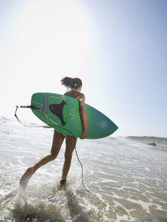 spattering: Hispanic girl running with surfboard