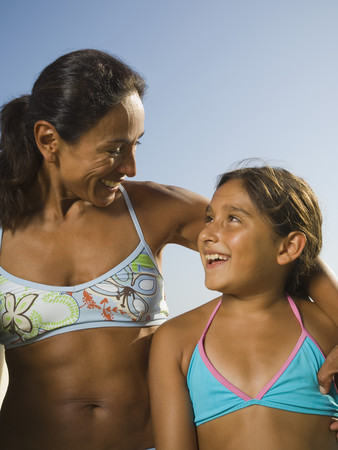 latina female: Hispanic mother and daughter smiling at each other