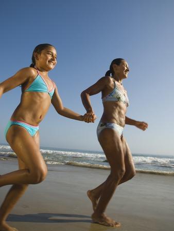 Hispanic mother and daughter running at beach