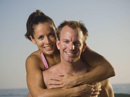 bathingsuit: Multi-ethnic couple hugging at beach LANG_EVOIMAGES