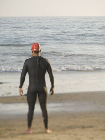 attired: Rear view of Hispanic man wearing wetsuit LANG_EVOIMAGES
