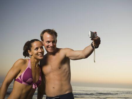 bathingsuit: Multi-ethnic couple taking own photograph LANG_EVOIMAGES