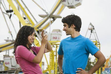 teenaged girl: Mixed Race teenaged girl taking photograph of boyfriend LANG_EVOIMAGES