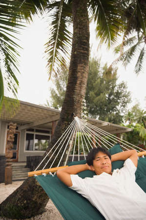 lighthearted: Asian man laying in hammock LANG_EVOIMAGES