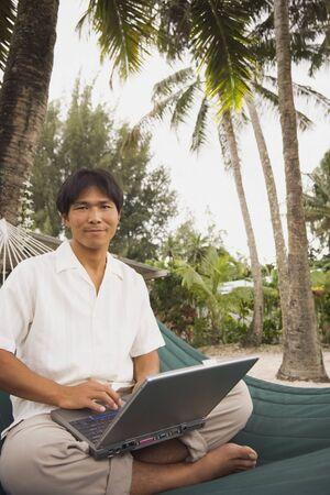 Aziatische man met een laptop in hangmat Stockfoto