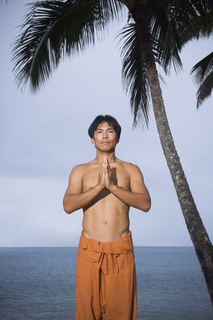 Asian man practicing yoga Stock Photo