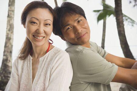 Asian couple sitting back to back Stock Photo